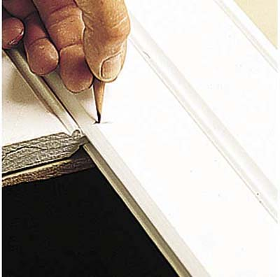 Marking cut lines with a pencil.
