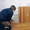 Tom Silva applying an adhesive before wainscoting