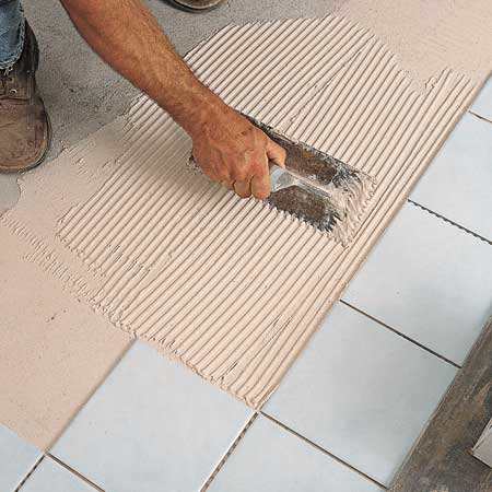 spreading adhesive to install tiles