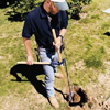digging a posthole for a picket fence