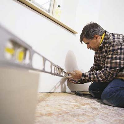 Tom Silva taking measurements for baseboard installing