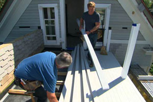 on the roof deck, Tom Silva and Kevin O'Connor install cellular PVC porch boards
