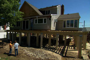 homeowner Carlos Santos and Kevin O'Connor look at a raised house in construction