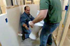 Richard Trethewey being handed a new toilet to install