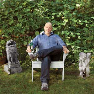 TOH editor Scott Omelianuk sits in his back yard with a beer between two stone gargoyles