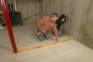 Tom Silva and homeowner frame a basement wall