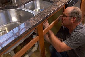 Richard Trethewey reattaches an undermount kitchen sink to a granite countertop