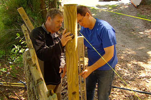 Roger Cook and homeowner replace a rotted fence post