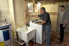 Richard Trethewey installs a washing machine in a basement
