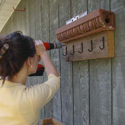 fasten cornice turned into garden tool holder to wall