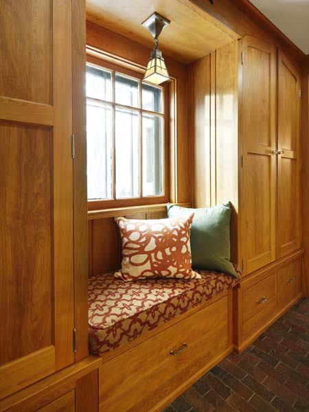 natural wood wrapping around a padded window seat with patterned fabrics and two complimentary pillows